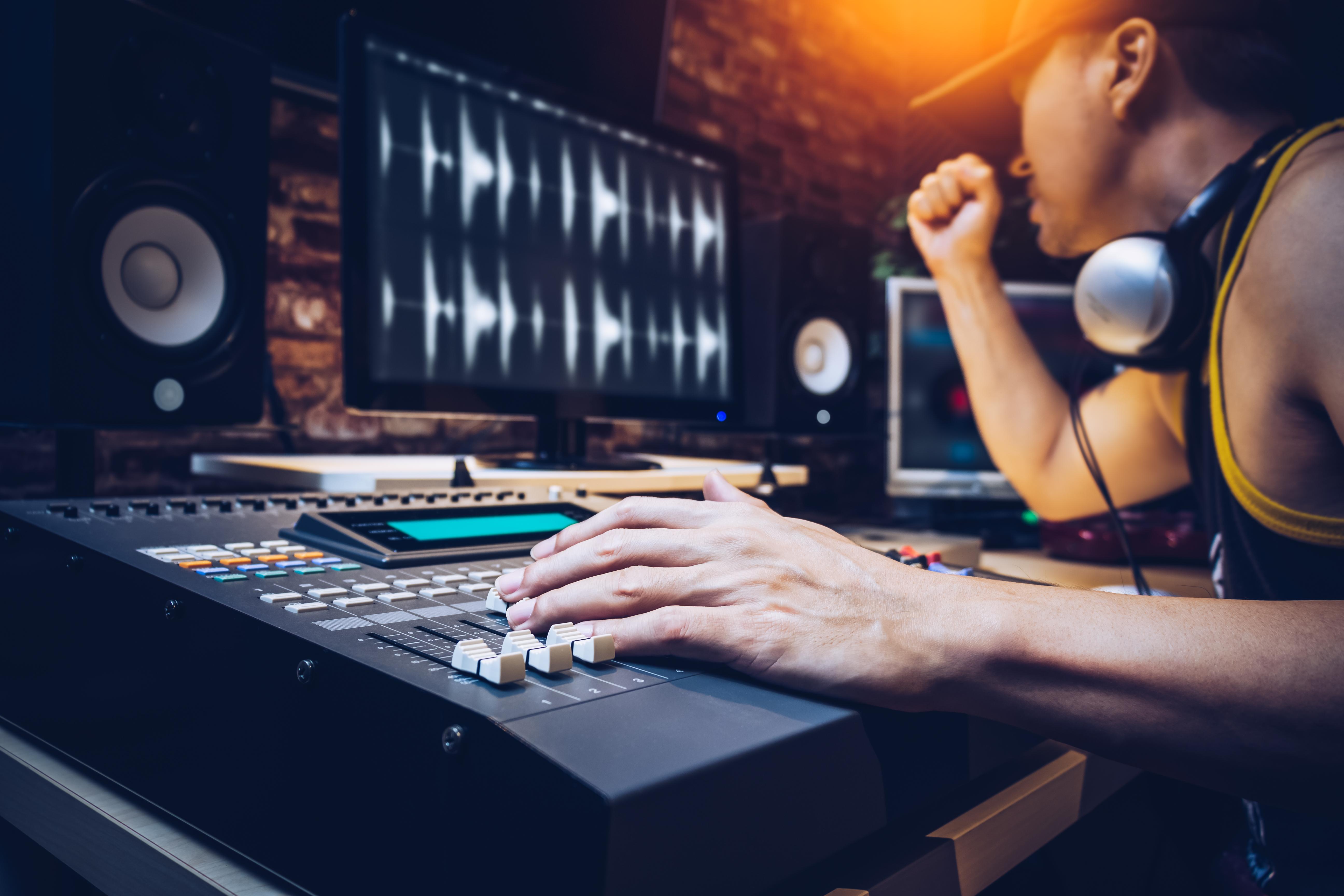 popular DJ working in radio broadcasting studio or music producer working in recording studio